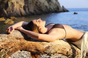 Beautiful woman sunbathing on a paradise beach in summer