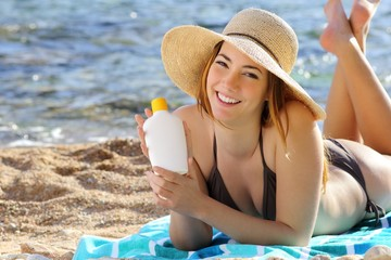 Happy woman on the beach showing a sunscreen bottle