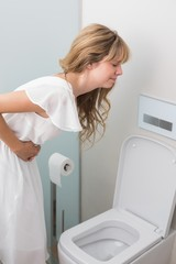 Woman with stomach sickness about to vomit into toilet