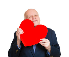 Old  senior man in love, holding red heart, on white background