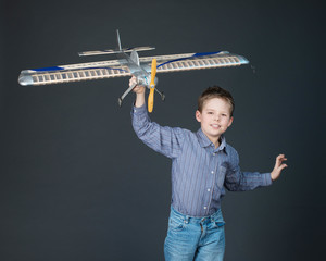 Happy boy playing with a wooden plane model