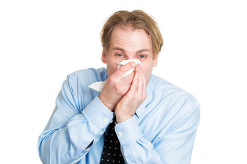 Sick man, blowing his runny nose, having allergy