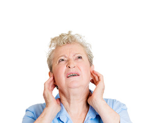 Loud noise upset stressed senior woman looking up
