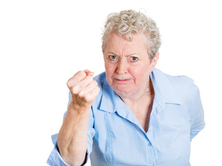 Angry elderly, senior woman, upset with someone, fist up in air