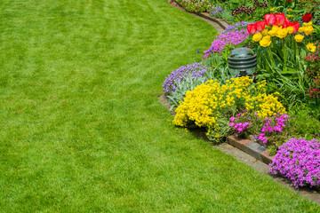 schöner Rasen mit Blumenbeet