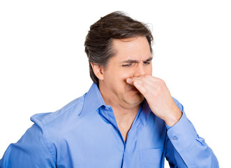 Bad smell. Man pinching his nose, can't tolerate odor