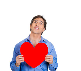 Young, peaceful man in love, holding red heart
