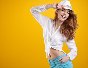 young happy girl in hat on yellow background