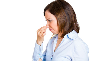 Woman pinches her nose, something stinks, unpleasant odor