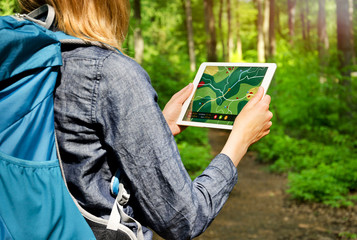 Hiking Woman using Tablet PC with Map outdoors