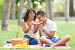 Portrait of a young couple with  eating watermelon at a picnic