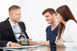 Businessman Showing House Picture To Couple On Laptop