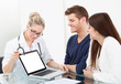 Doctor Showing Report To Couple On Laptop