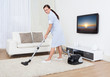 Maid Cleaning Carpet With Vacuum Cleaner