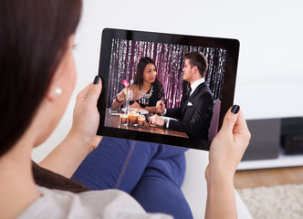 Young Woman Watching Movie At Tablet