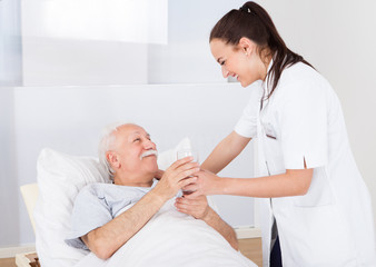 Doctor Giving Glass Of Water To Senior Man
