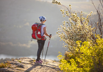 Young female hiker standing on cliff and enjoying valley view