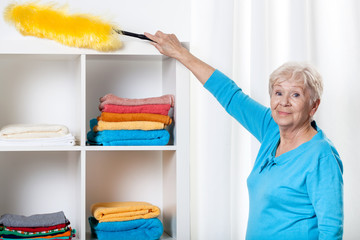 Elderly woman using duster