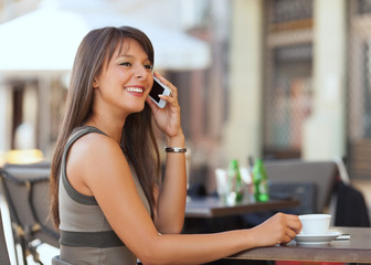 Cheerful young businesswoman talking on the phone