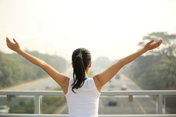 woman stand at the pedestrian overpass open arms to driveway