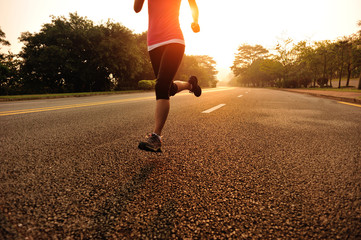 Runner athlete running on sunrise road