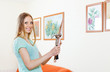 Positive  woman hanging pictures on wall