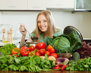 happy long-haired woman cooking with heap of  vegetables