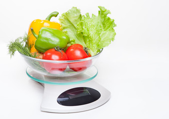 Kitchen weight scale with vegetables.