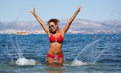 Attractive girl playing in the sea with a splash of watern