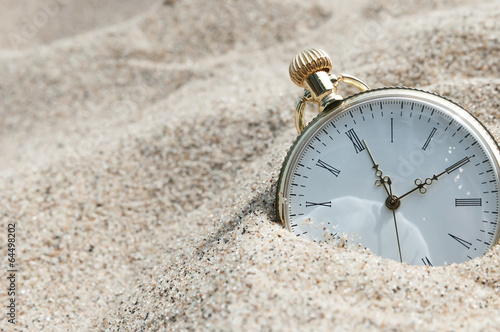 Pocket watch buried in sand - 64498202