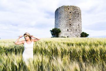 Femme blonde espiègle dans un champ de blé.
