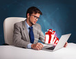 Handsome man sitting at desk and typing on laptop with present b
