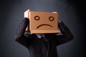 Businessman gesturing with cardboard box on his head with sad fa