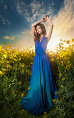 Fashion beautiful young woman in blue dress posing in sunset