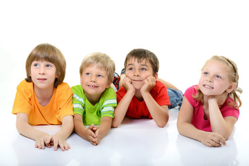 cute children in colored t-shirts lying and smiling looking with