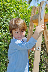 The  boy with a smile poses on step-ladder