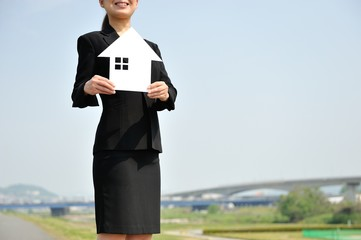 住宅の模型を持つ女性
