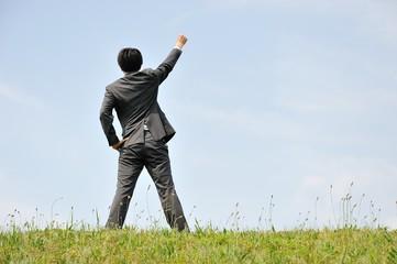 空に向かって立っているスーツの男性ビジネスマン