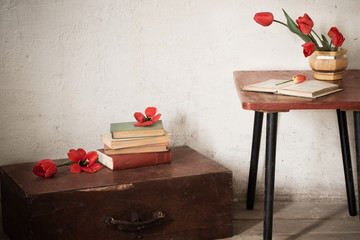 Vintage old  suitcase with old books and red tulips on floor