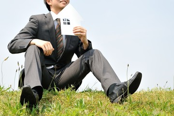 白い家を持って草の上に座っているスーツのビジネスマン
