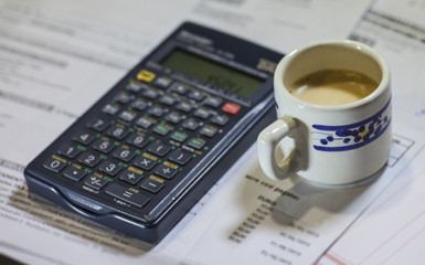Utility bills, coffee and calculator