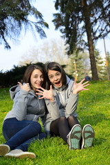 Two young woman expressing agreement and excitement in a park