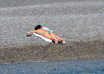 Woman sunbathing on the sea beach