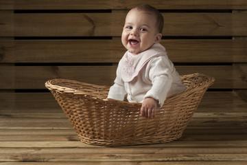 bebe recien nacido riendo dentro de una cesta fondo de madera