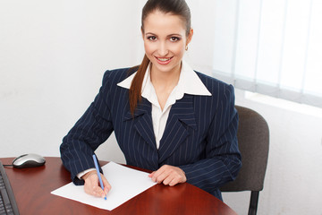 Happy businesswoman write on blank paper with pen