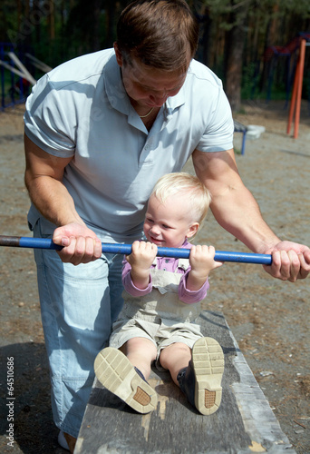 Dad and his little son do exercises