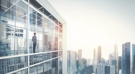 Businessman standing on a balcony and looking at city