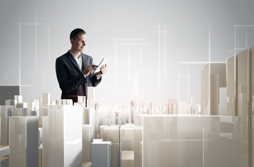 Businessman with tablet PC working with a modern city project