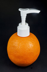 Press the orange bottle of lotion On a black background