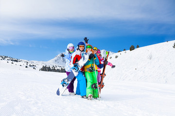 Five friends together with snowboards and skis